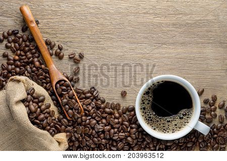 Coffee cup with beans wood spoon and hemp sack bag on wood table top view
