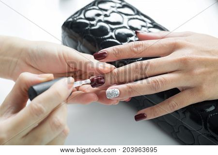 Manicure and pedicure series: Manicurist applying clear nail polish on customer's gel nail