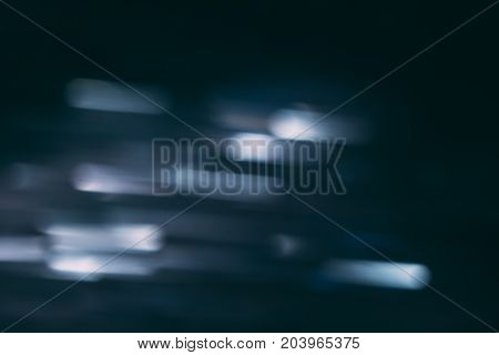 Abstract background of defocused white lights in motion. Glowing urban backdrop, heavy night illumination city glimmers, bokeh