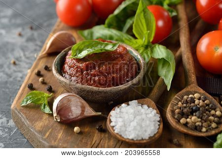 Tomato sauce with basil on a gray background