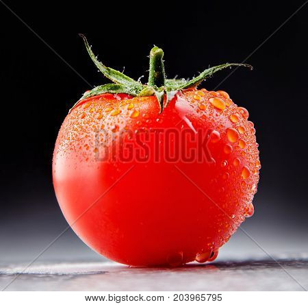 Juicy tomato with drops in the studio.