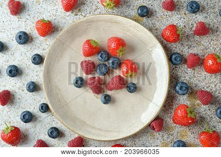 Fresh berries in a plate on a brown background