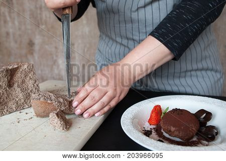 Cook woman breaks off piece of chocolate for decoration of delicious fondant in restaurant. Process of making culinary art, close up picture