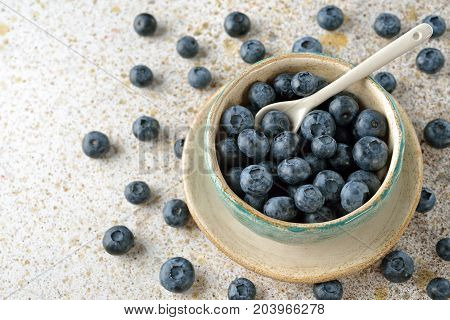 Fresh organic blueberries in a bowl on a brown background