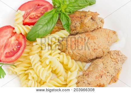 Top view of the braised stuffed meat roulades spiral pasta and tomato decorated with basil and parsley twigs closeup