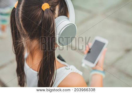 little child with headphones and phone in hand, cute teenager listening to music in white headphones, girl with pigtails looks at the phone