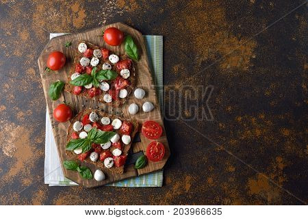 Bruschetta with mozzarella and basil on a brown background