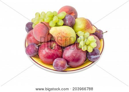 Several apples pears plums peaches and clusters of white grapes on the big yellow dish on a white background