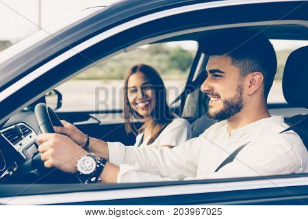 Side view of a happy young man driving a car with his girl friend beside him