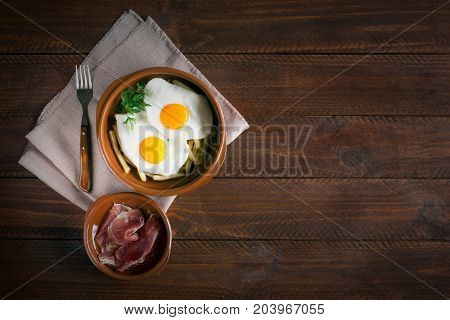 Traditional spanish lunch - fried eggs with french fries, cured pork slices of jamon on the dark wooden table