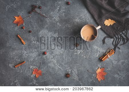Autumn composition. Cup of coffee blanket autumn leaves cinnamon sticks on black background. Flat lay top view