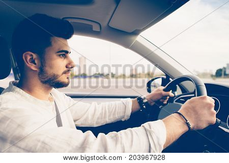 Side view of a young man is driving a car with a security position