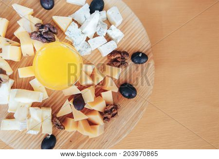 assortment of different kinds of cheeses with nuts and honey on a wooden background