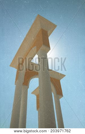Architecture. Retro film effect image. Arch columns against the sky in front of the sun