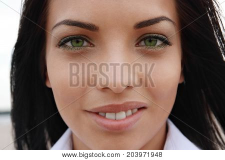 Beautiful green-eyed mulatto girl looks into the camera close-up outdoors