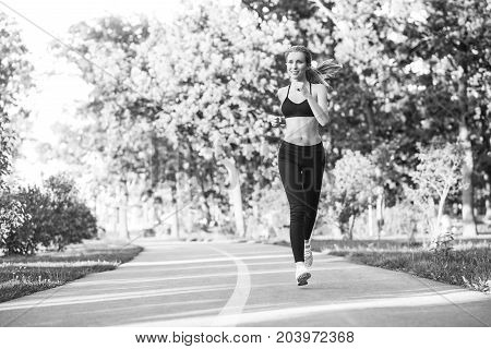 Monochrome shot of a young beautiful female athlete enjoying running in the forest smiling looking away copyspace positivity active lifestyle fit toned energetic concept.