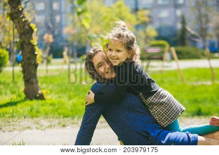 Little girl hugs mother sitting on the grass. Child playing threw his mother on grass. Family in spring walks on street.