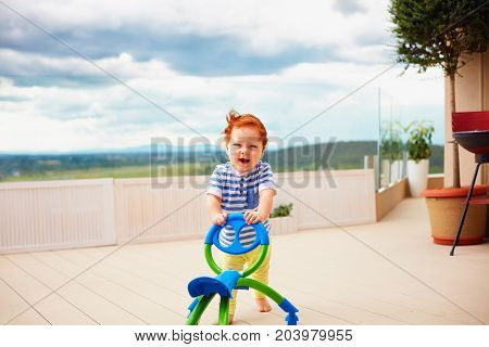 A Toddler Baby Boy Pushing Pushing Go Cart, Outdoors