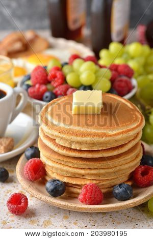 Pancakes with berries on a brown background