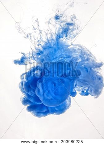 Blue ink swirl in water isolated on white background. The paint in the water. Soft dissemination a droplets of blue ink in water close-up. Abstract vertical photo with soft focus, blurred backdrop.