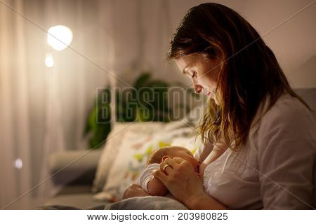 Young Beautiful Mother, Breastfeeding Her Newborn Baby Boy At Night