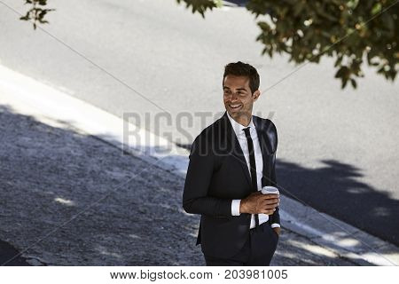 Smiling businessman in suit with coffee smiling