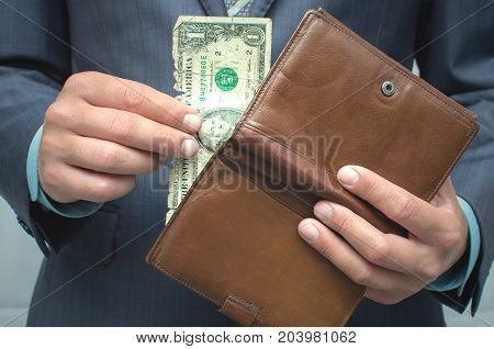 Savings. Poverty. Pay the debts. The man in the suit pulls out one last dollar from wallet.