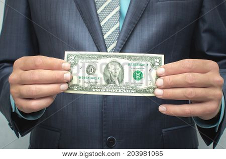 Savings. Poverty. Pay the debts. The man in the suit holding two dollar banknote in hands in front of him.