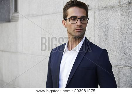 Seriously smart businessman in glasses looking away