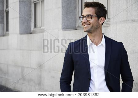 Happy businessman in suit and glasses looking away