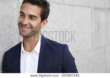 Happy handsome guy in suit smiling and looking away