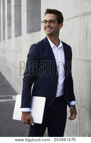 Handsome Businessman holding laptop in city smiling