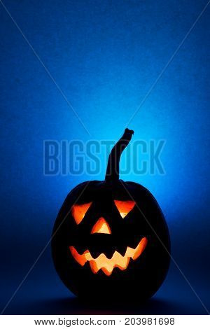 Halloween pumpkin, silhouette of funny face on blue background. Vertical.