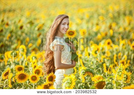 Woman with long hair stands in a field of sunflowers and smiles.