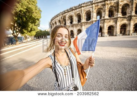 Young woman tourist making selfie photo in front of the ancient amphitheatre in the old town of Nimes during the sunny morning in France