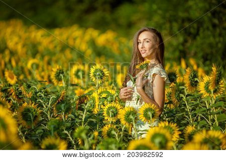 Woman among yellow sunflowers in the field.
