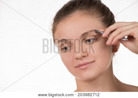 Young beautiful girl pulls out her eyebrows with tweezers metal on a white background