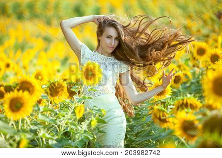 In the field with sunflowers is a woman her long hair fluttering.