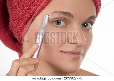 Young beautiful girl in a red towel caring for your eyebrows with trimmer
