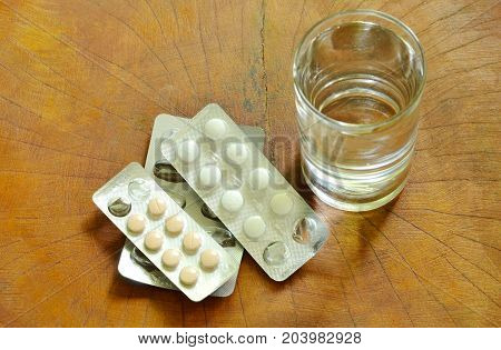 medicine in blister pack with fresh water on table