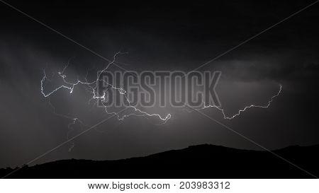 Panoramic view of Lightning strike over mountain range