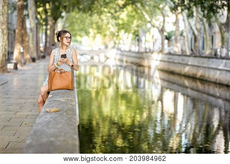 Young stylish business woman sitting with phone and bag outdoors at the beautiful park with river during the sunny day