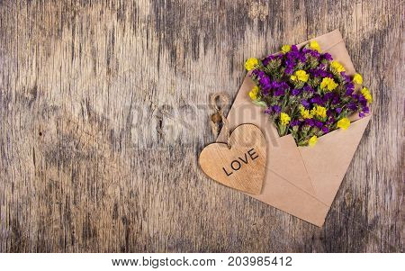 Envelope with flowers. Wildflowers in an envelope. Heart made of wood. Romantic concept.