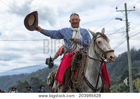 May 27 2017 Sangolqui Ecuador: cowboy raising his hat in greeting while riding a horse towards a rural rodeo in the Andes