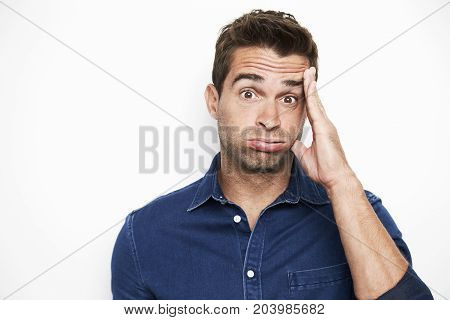 Disbelieving dude in blue shirt portrait studio