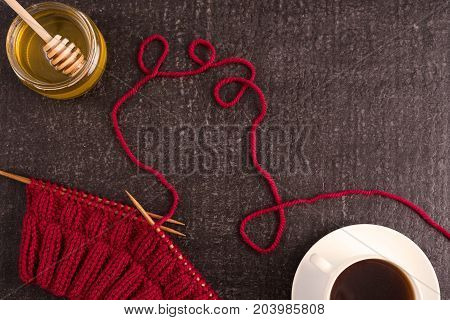 Composition with coffee, honey and red knitting on a black background.