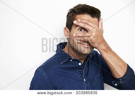 Guy in blue shirt peeking out from hand over eyes