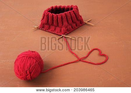Dark red knitting on a brown grunge background.