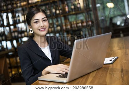 Asian Woman Using Laptop In Restaurant With Attractive Smiling, Woman Working Concept