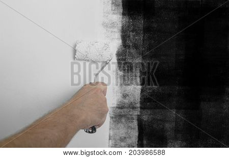 Black and white wall. Decorator's hand painting wall with roller.